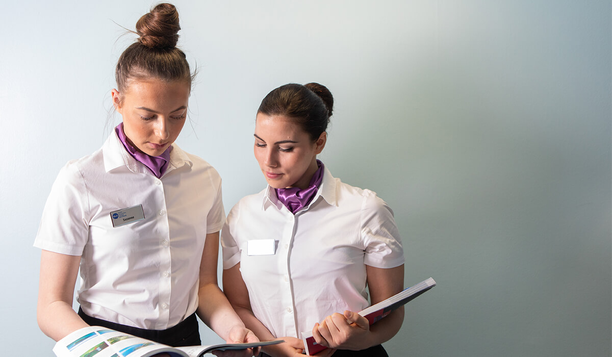 Two women dressed as air steward attendants looking at maps