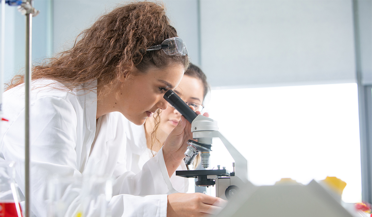 Woman looking through science equipment